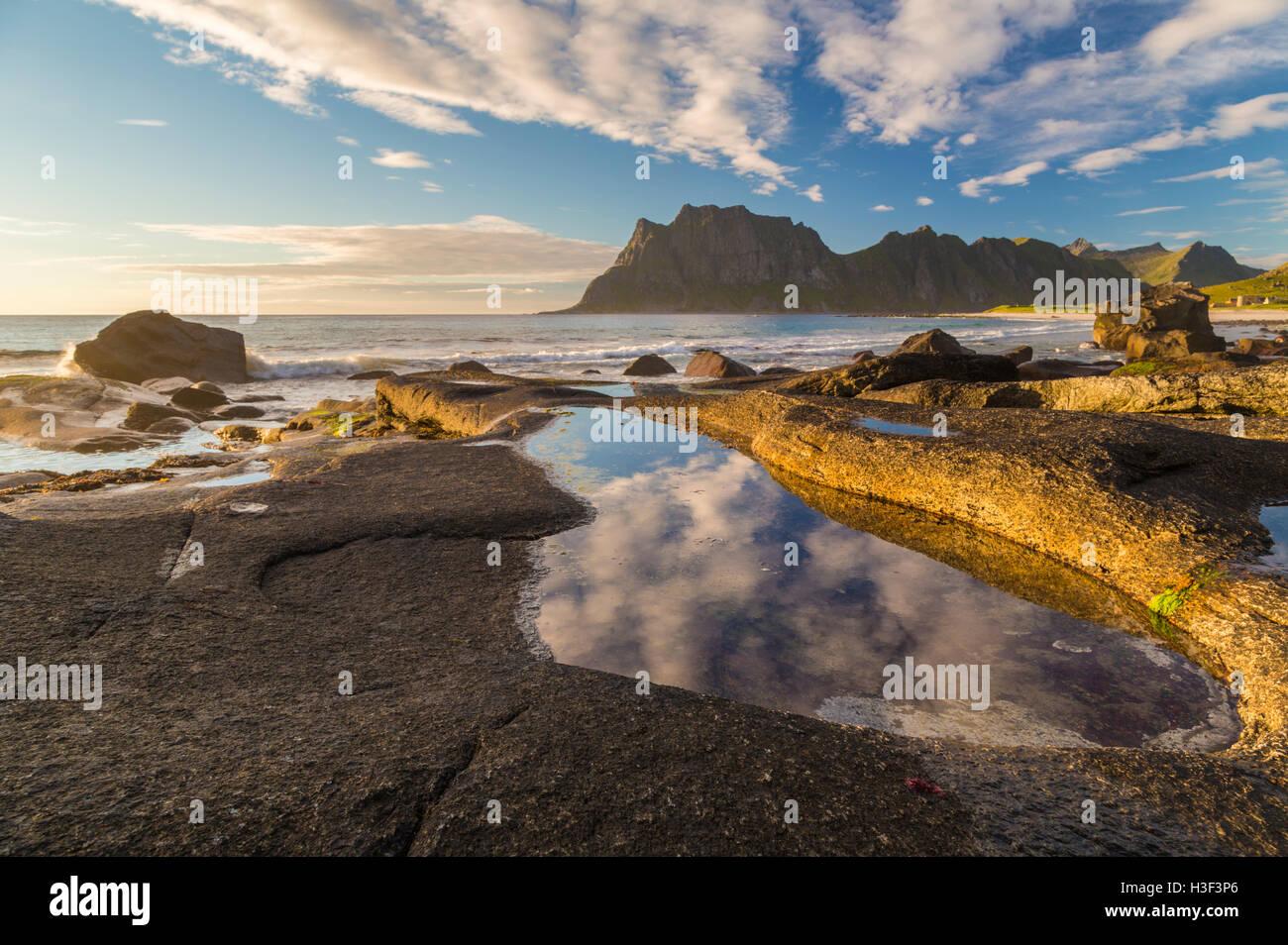 Rocas en luz del atardecer con una cálida luz brilla sobre ellos con Sky reflejando en un charco de agua, altas Imagen De Stock