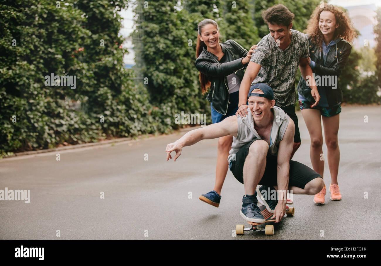 Disparo de longitud completa de adolescentes chicos en patineta con niñas empujando. Grupo multiétnico de amigos Foto de stock