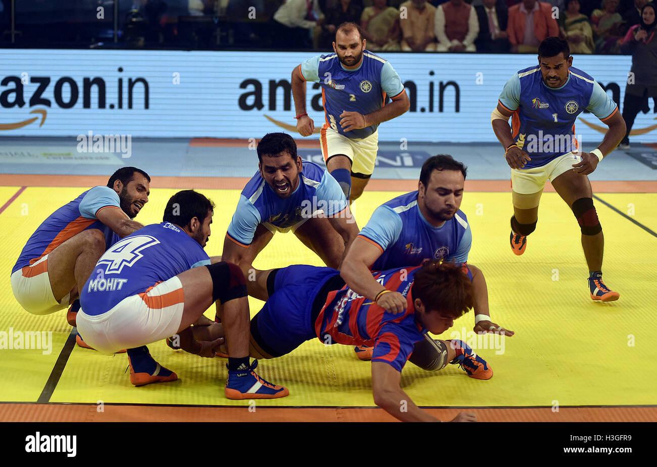 En Ahmedabad, India. 7 Oct, 2016. Indian jugadores abordar un jugador de Corea del Sur (abajo) durante el partido Imagen De Stock
