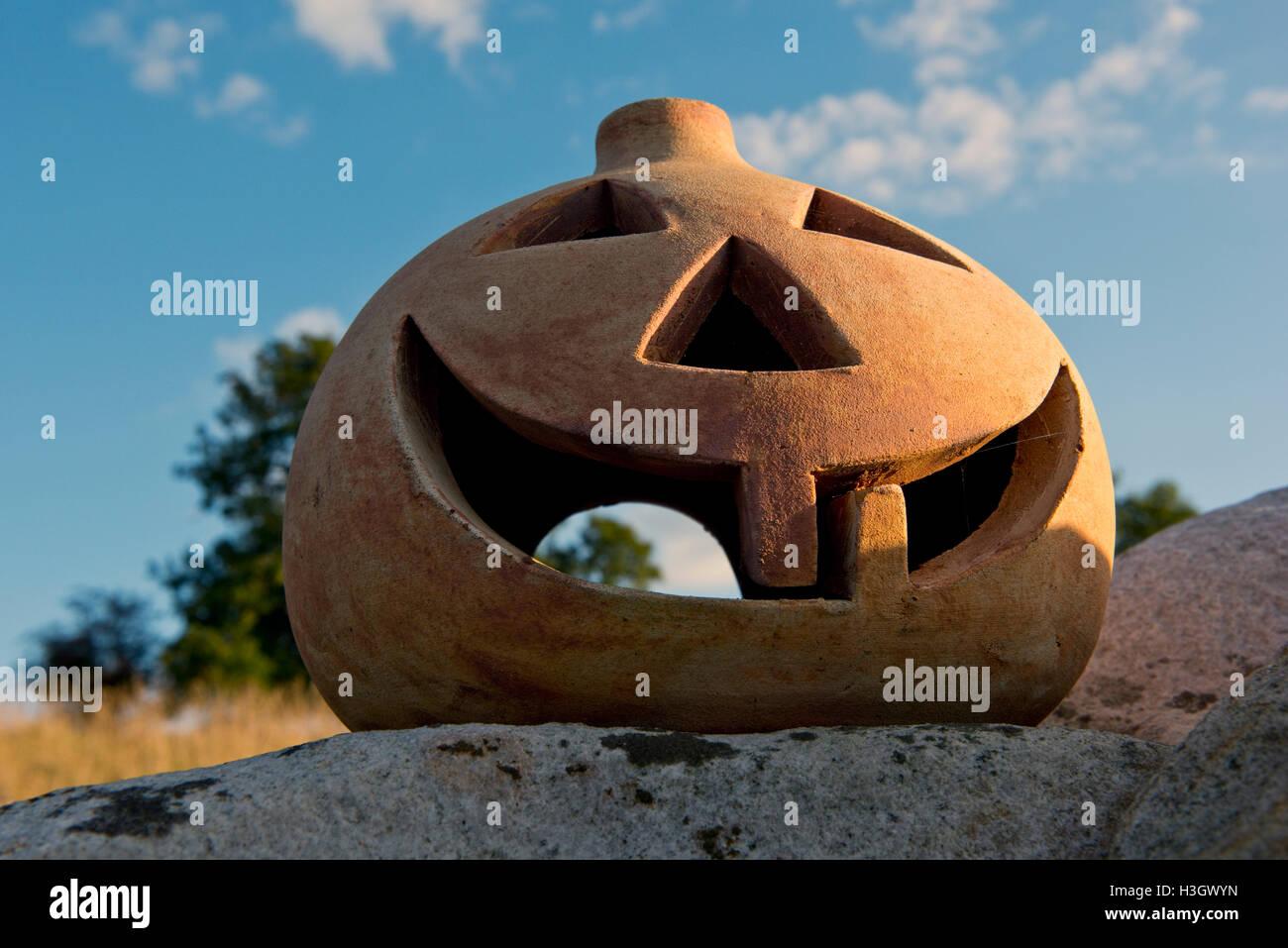 Una calabaza de terracota con los ojos, la nariz y la boca y dos dientes, listo para Halloween Foto de stock