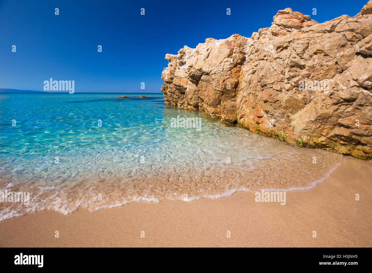 Hermosa playa de arena con zonas de rocas y agua clara tourquise cerca Cargese, Córcega, Francia, Europa. Imagen De Stock