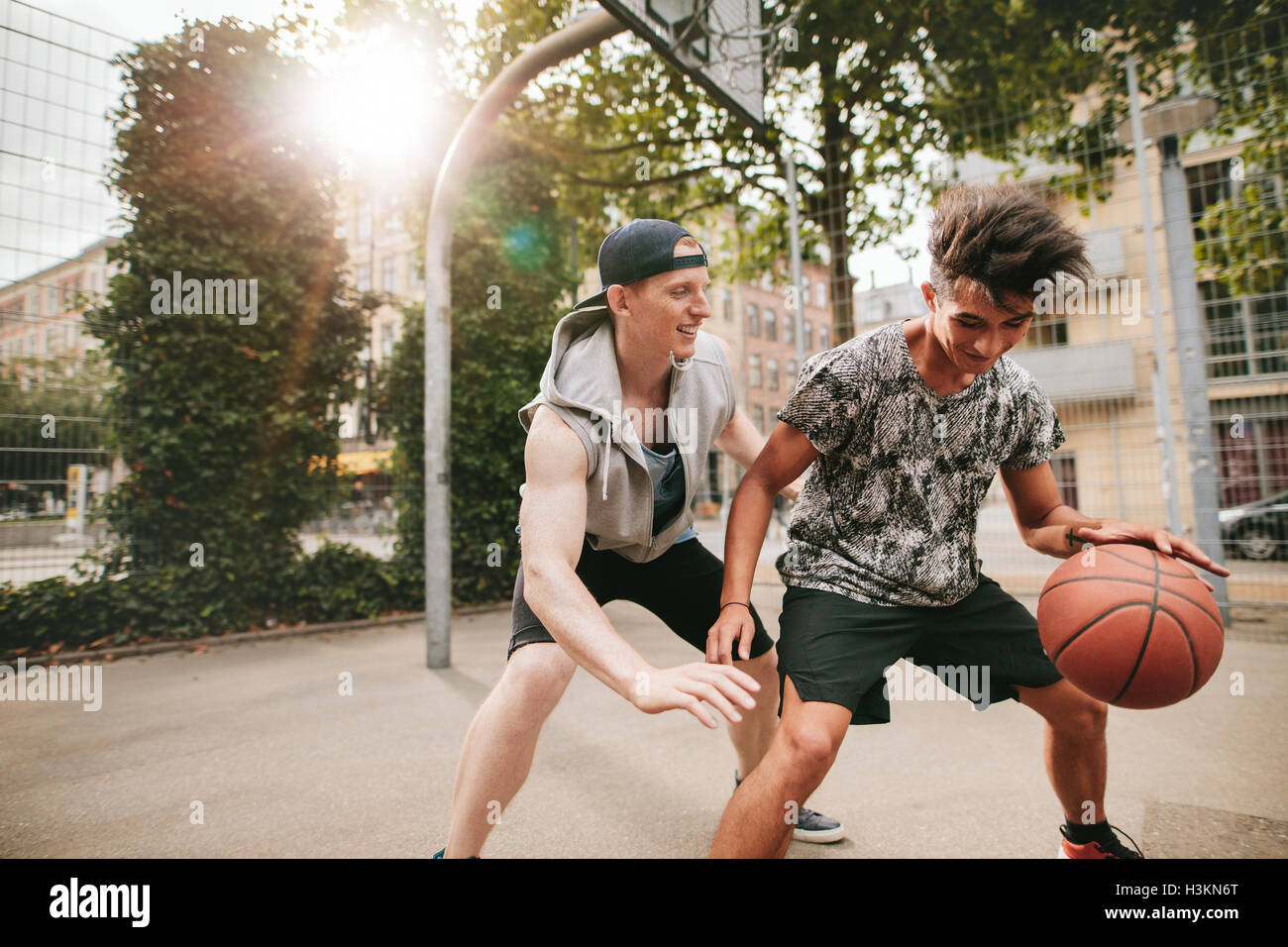 Dos jóvenes amigos jugando baloncesto en la cancha al aire libre y divertirse. Streetball jugadores tienen Imagen De Stock