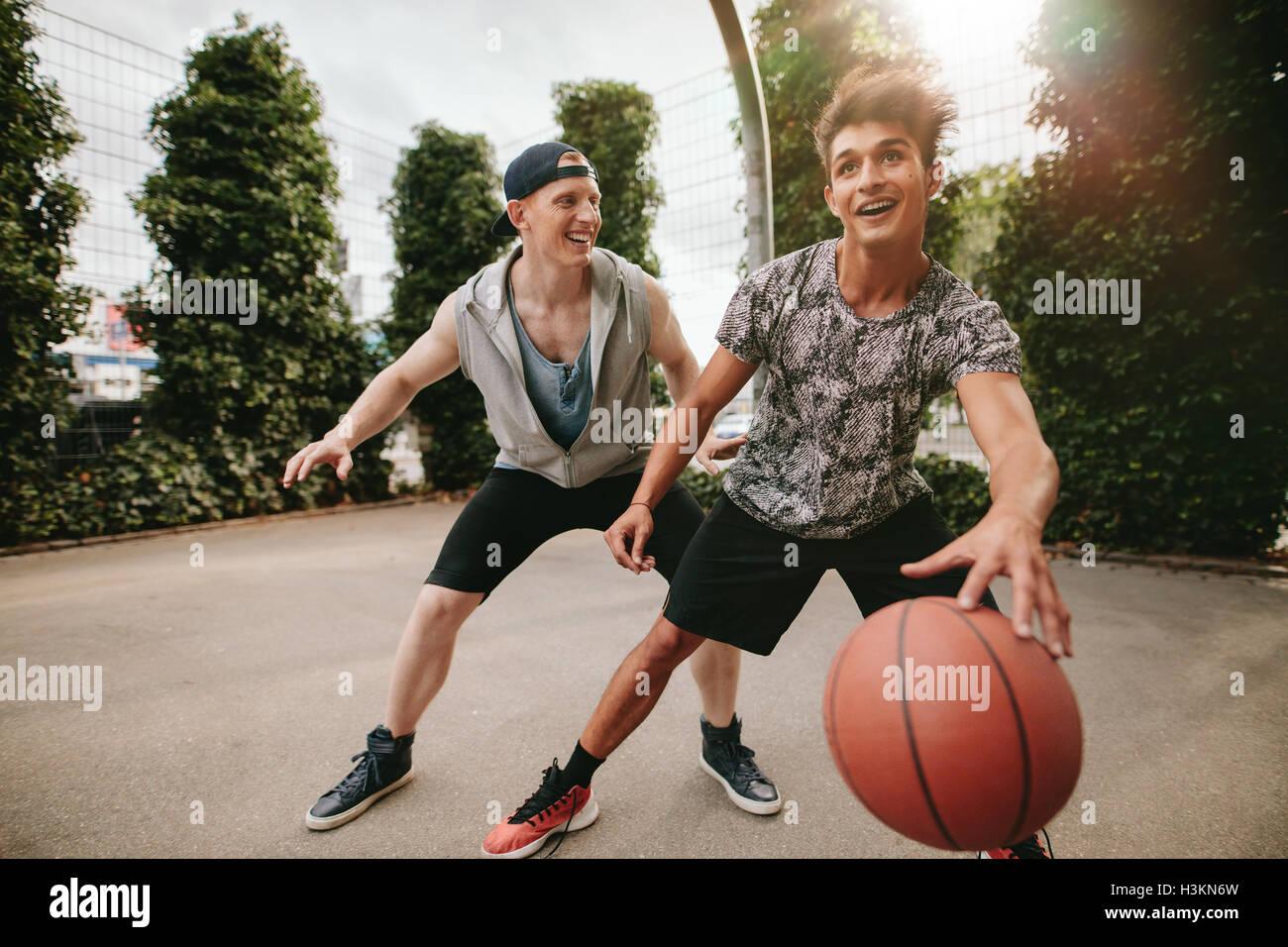 Dos jóvenes amigos jugando y divirtiéndose. Streetball jugadores tienen un juego de básquetbol en Imagen De Stock