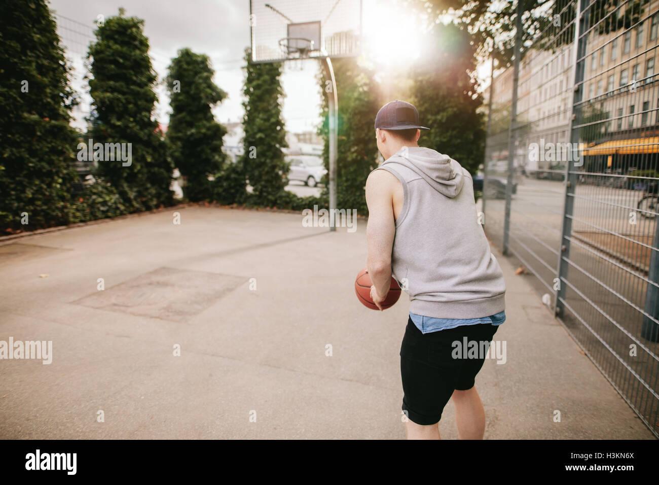 Vista trasera de la foto de un jugador de streetball jugando básquetbol. Joven jugando baloncesto en el tribunal Imagen De Stock