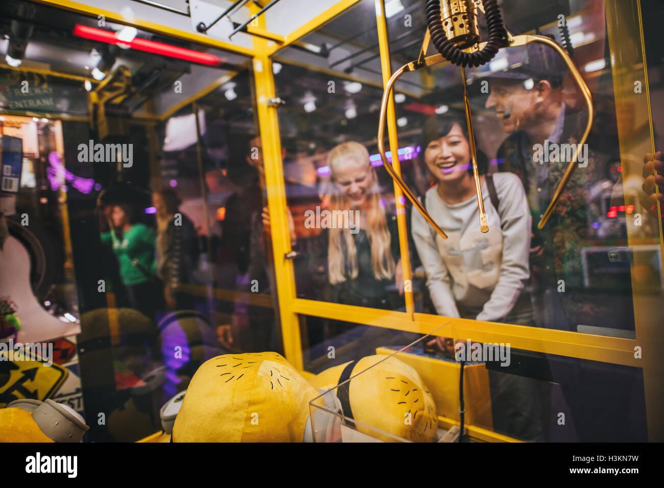 Mujer joven feliz jugando toy agarrando juego con amigos en el parque de diversiones. Imagen De Stock