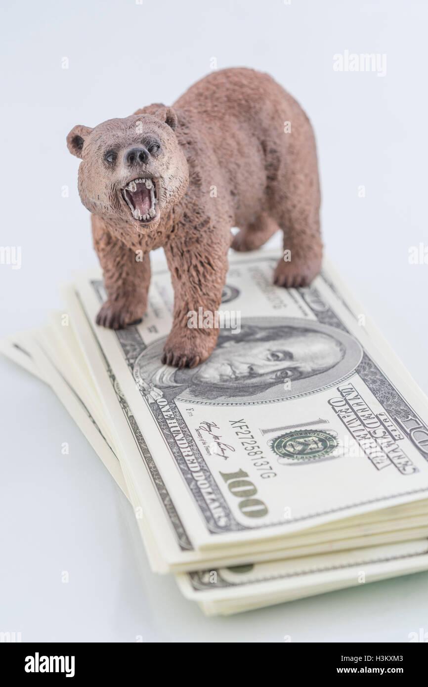 Oso con pila de US$ 100 Franklin billetes / billetes, como metáfora del concepto de los mercados financieros Bull Foto de stock