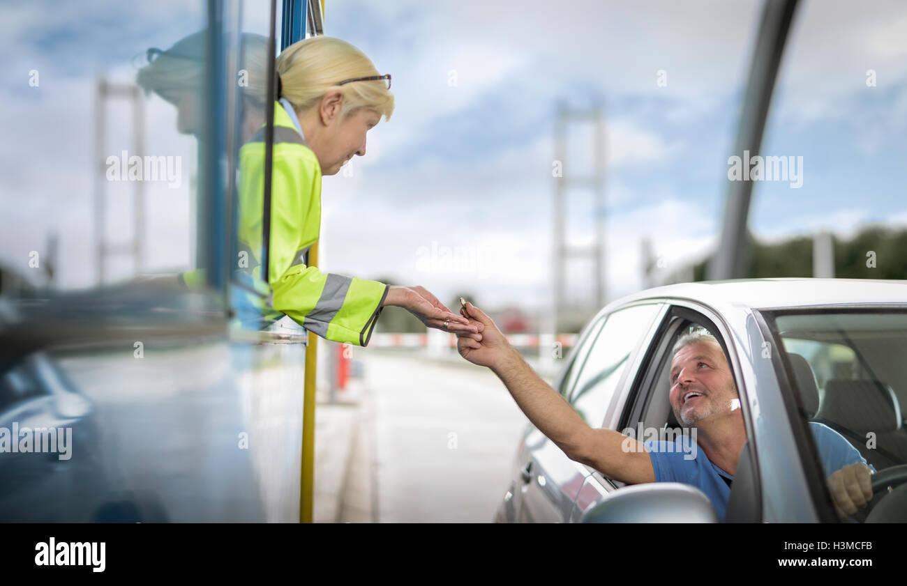 Conductor en coche pagando peaje al puente Imagen De Stock