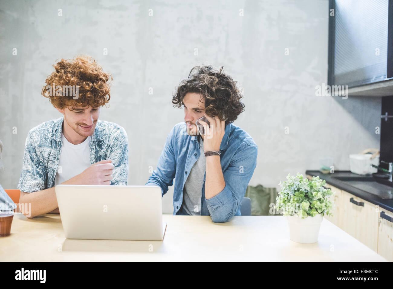 Co-trabajadores trabajando en el portátil en la oficina Foto de stock