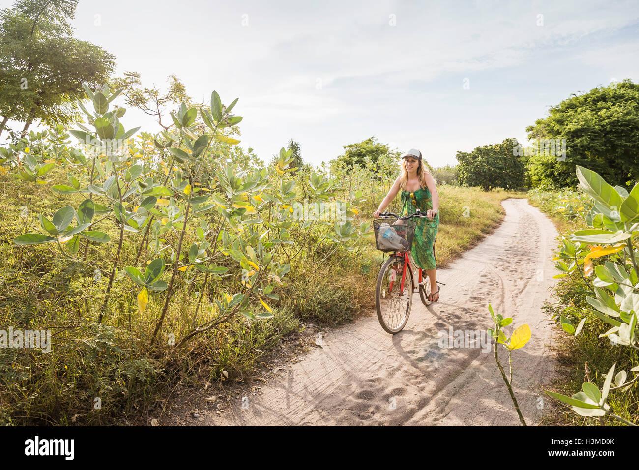 Mujer joven ciclismo en pista de tierra, Gili Meno, Lombok, Indonesia Foto de stock
