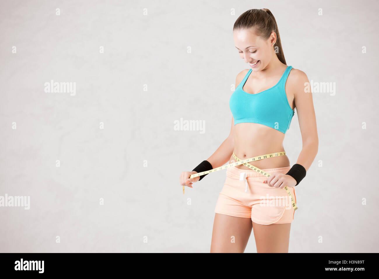 Mujer midiendo su cintura con una cinta de medición amarilla, aislado en blanco Imagen De Stock