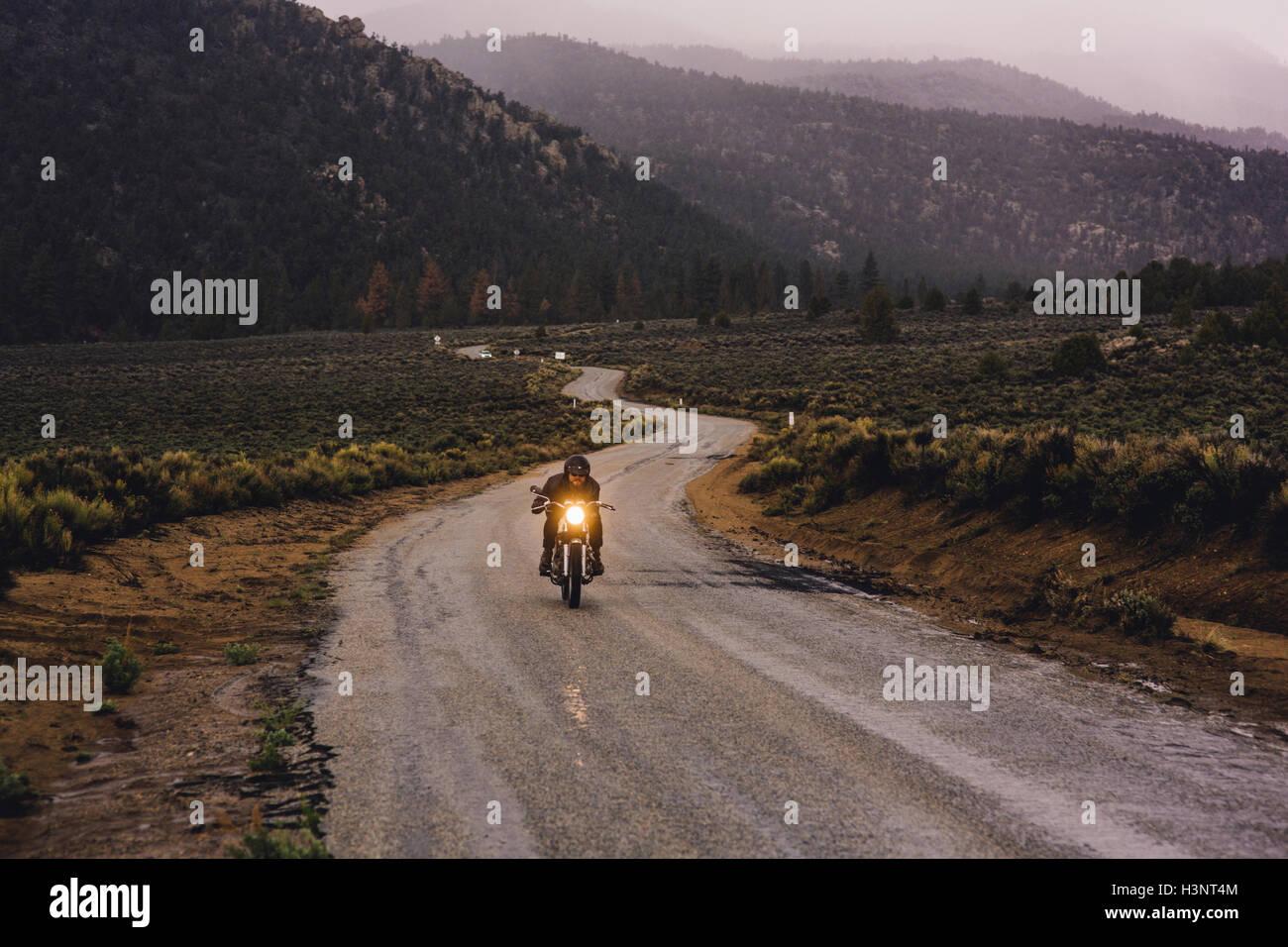 El motorista montando moto en carretera abierta, Kennedy Meadows, California, EE.UU. Foto de stock