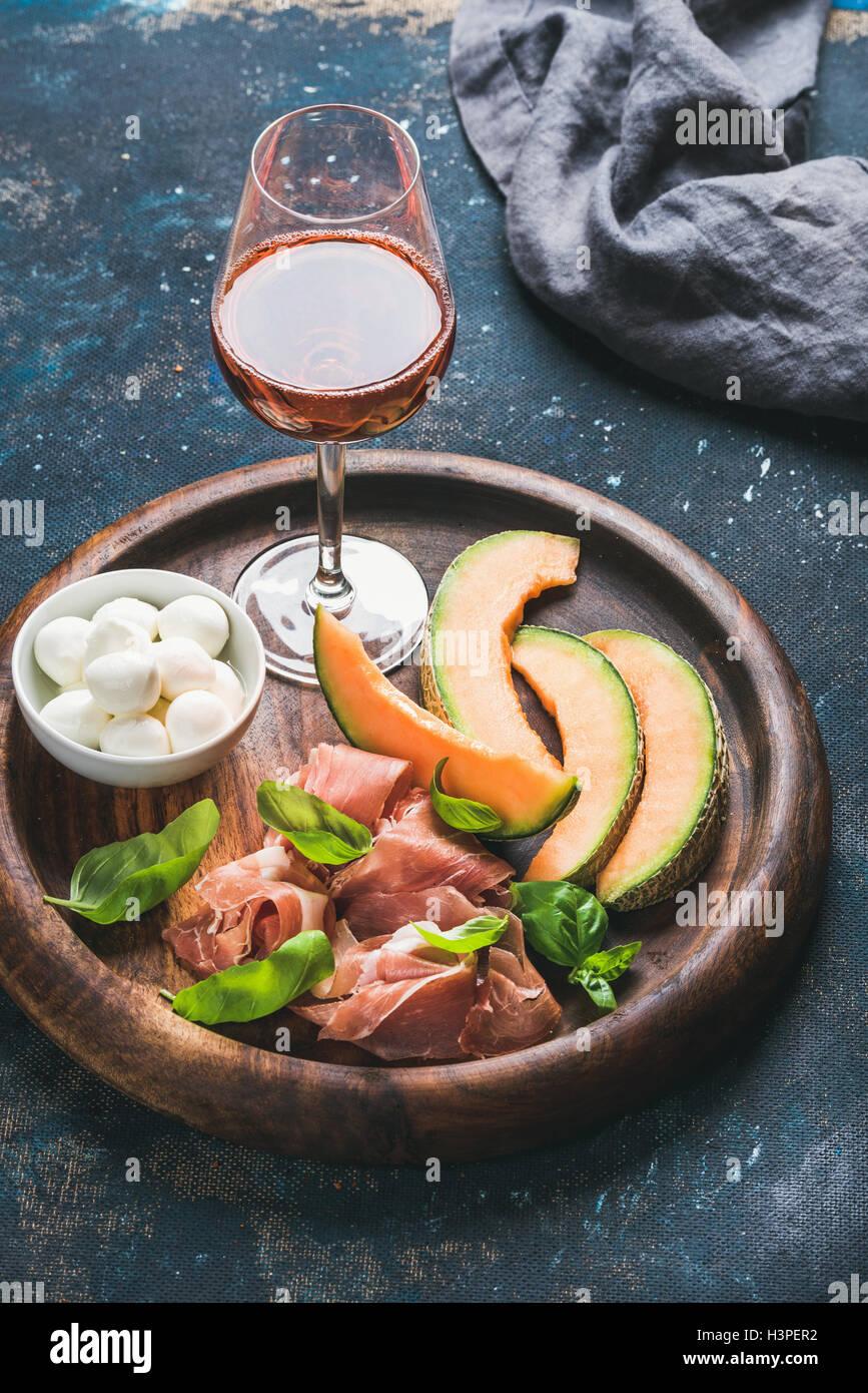 Prosciutto, melón, queso mozzarella y vidrio de rosa Imagen De Stock