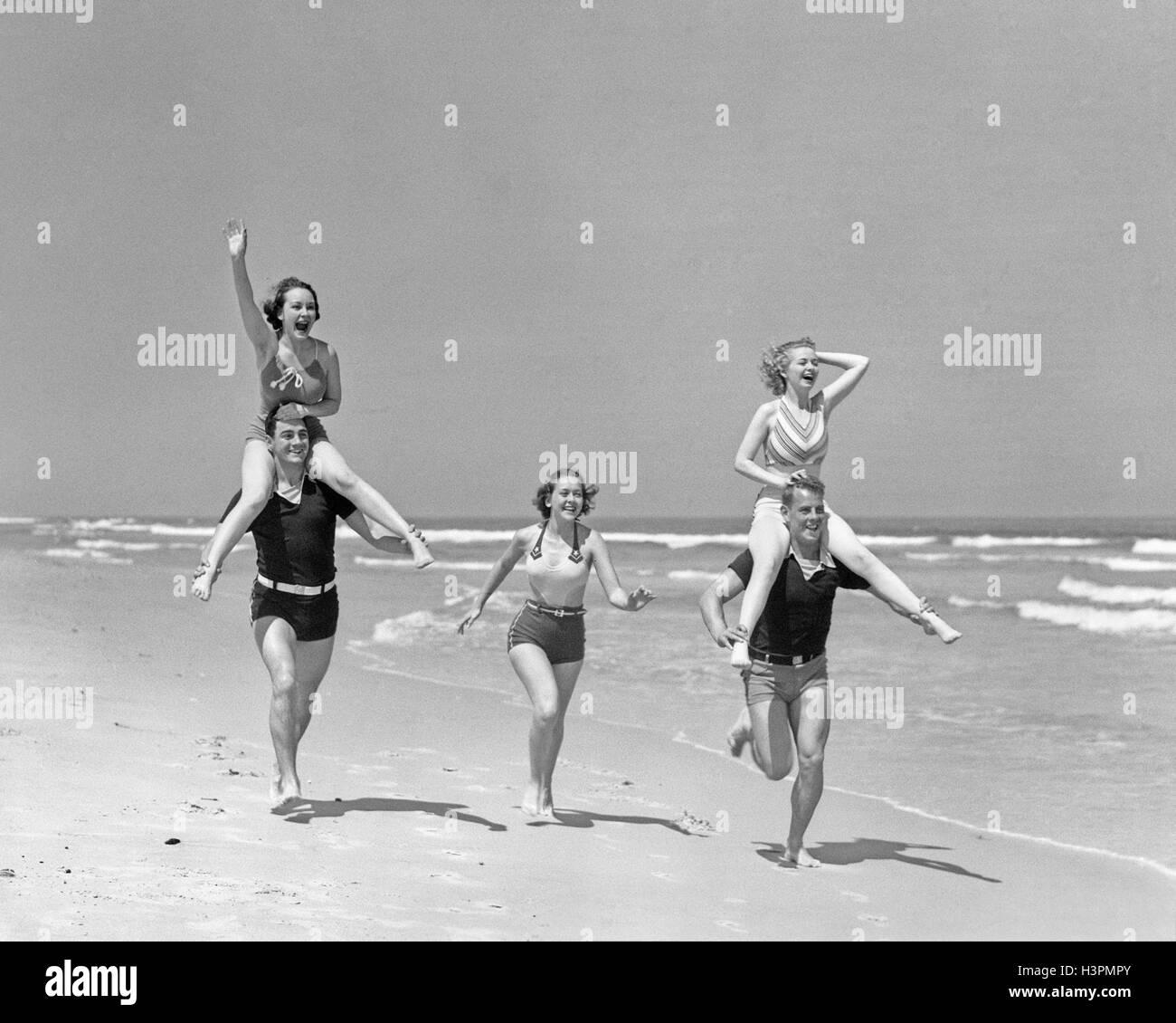 Grupo de 1930 HOMBRES MUJERES RUNNING DESCONTROL EN LA PLAYA MUJERES cabalgando sobre los hombros del mens Imagen De Stock
