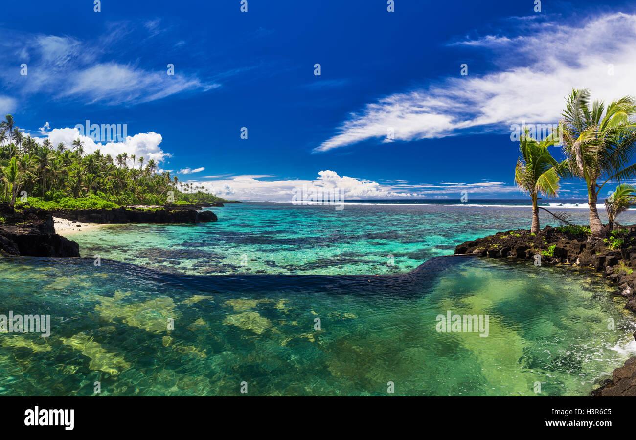 Infinity pool de roca natural con palmeras a lo largo de los océanos tropicales laguna Foto de stock