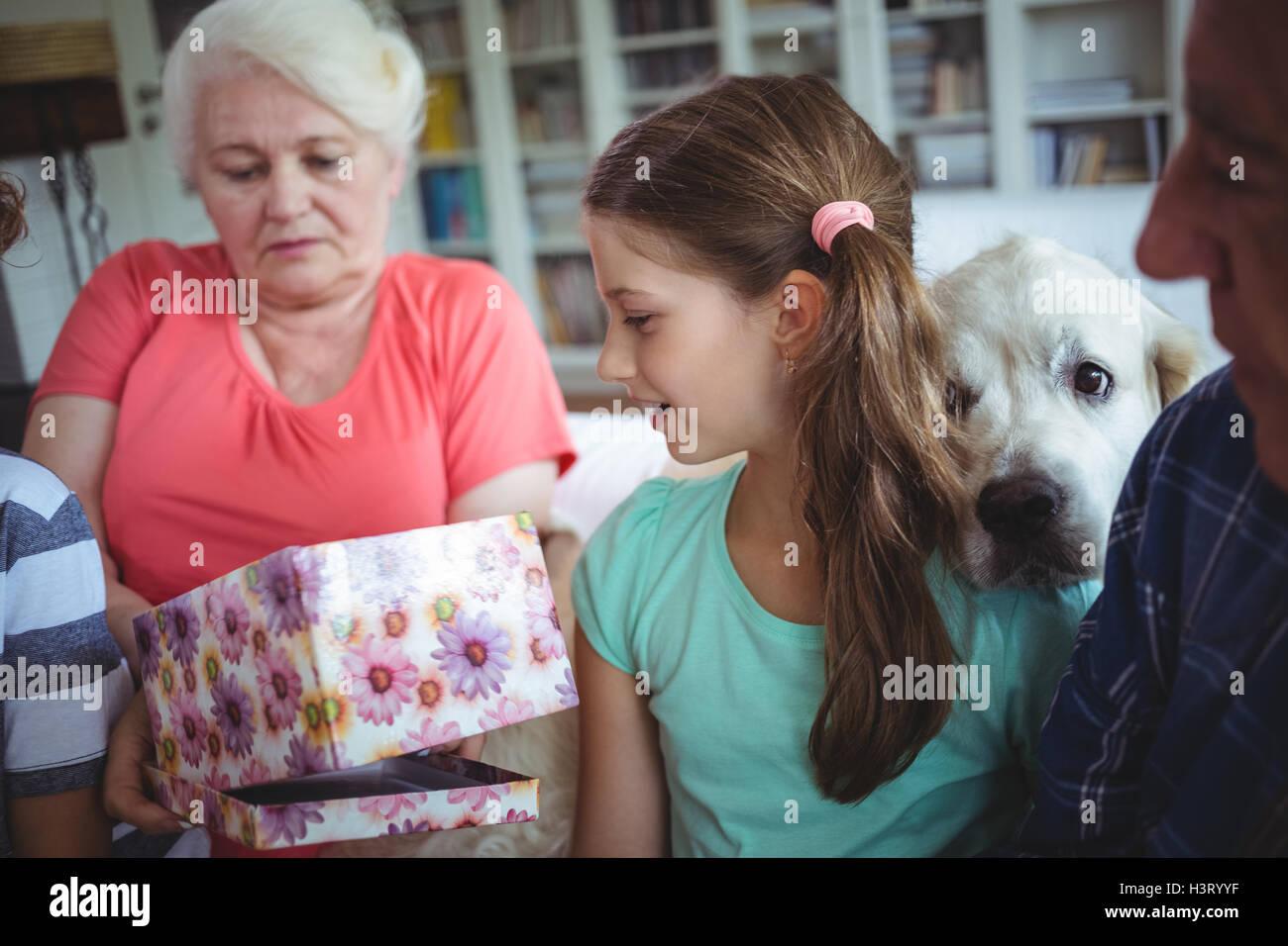 Abuelos y nietos mirando regalo sorpresa en la sala de estar Imagen De Stock