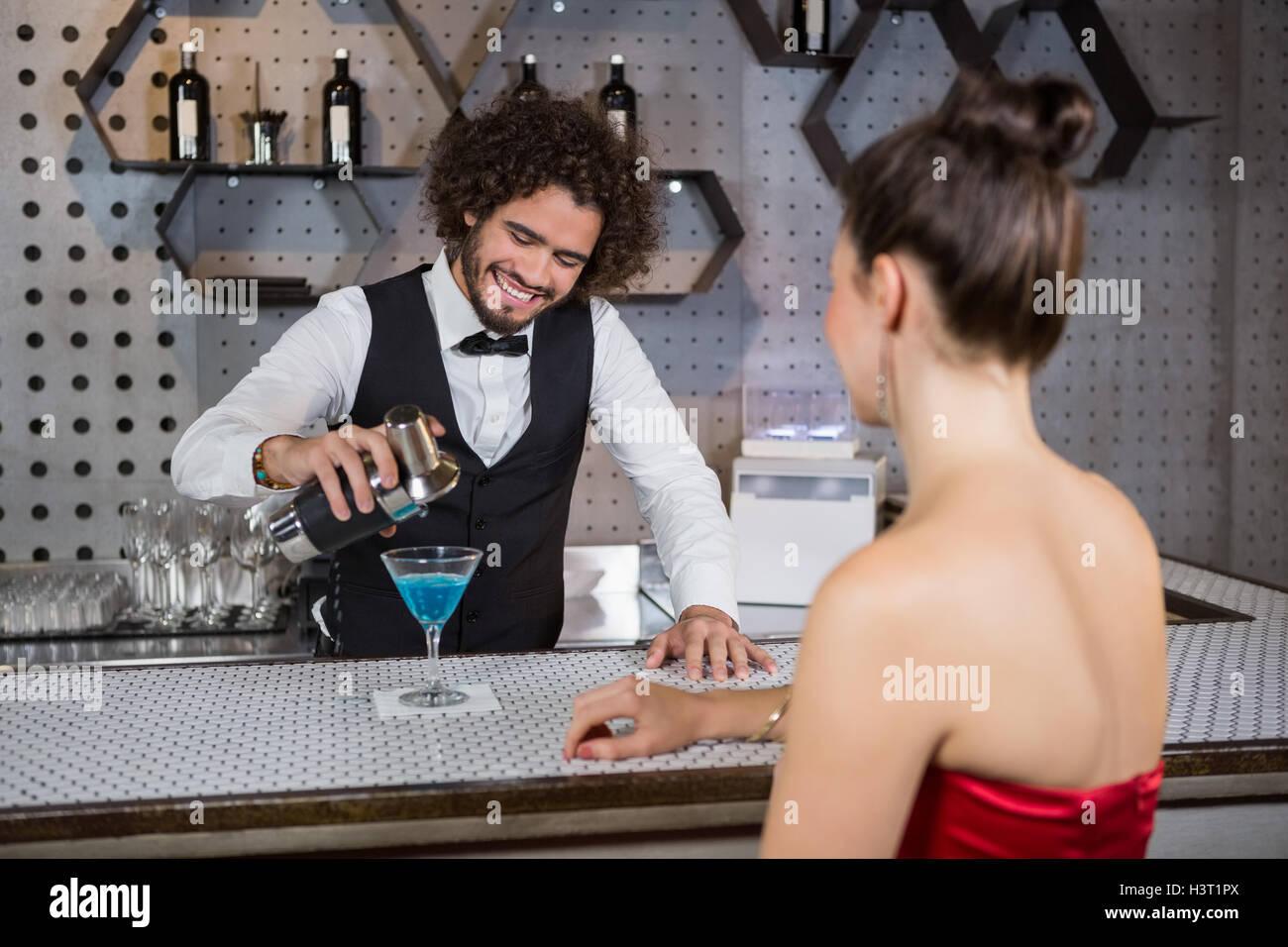 Verter camarero cóctel en womans cristal en el mostrador de bar Imagen De Stock
