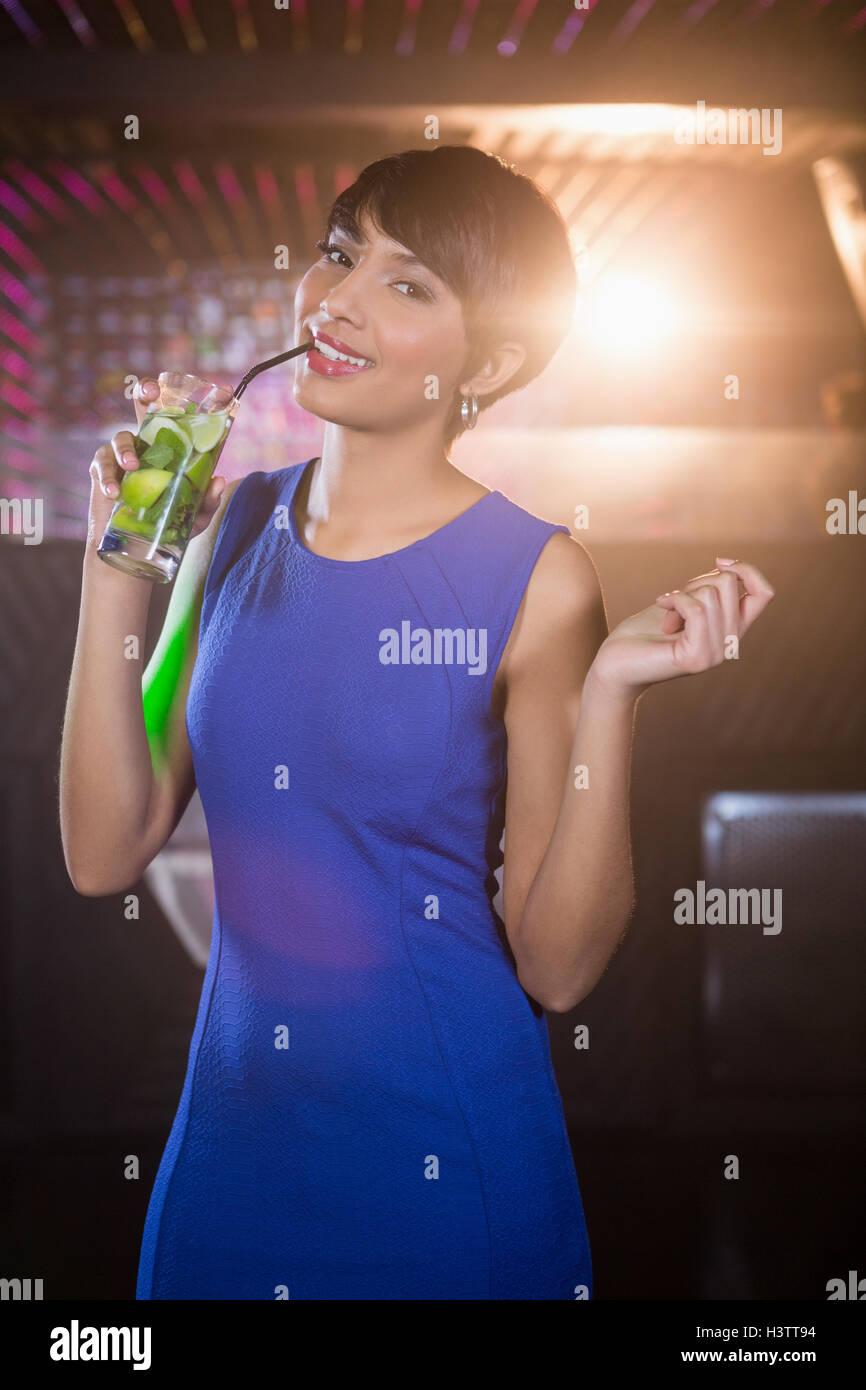 Mujer joven bailando en la pista de baile mientras habiendo cóctel Imagen De Stock