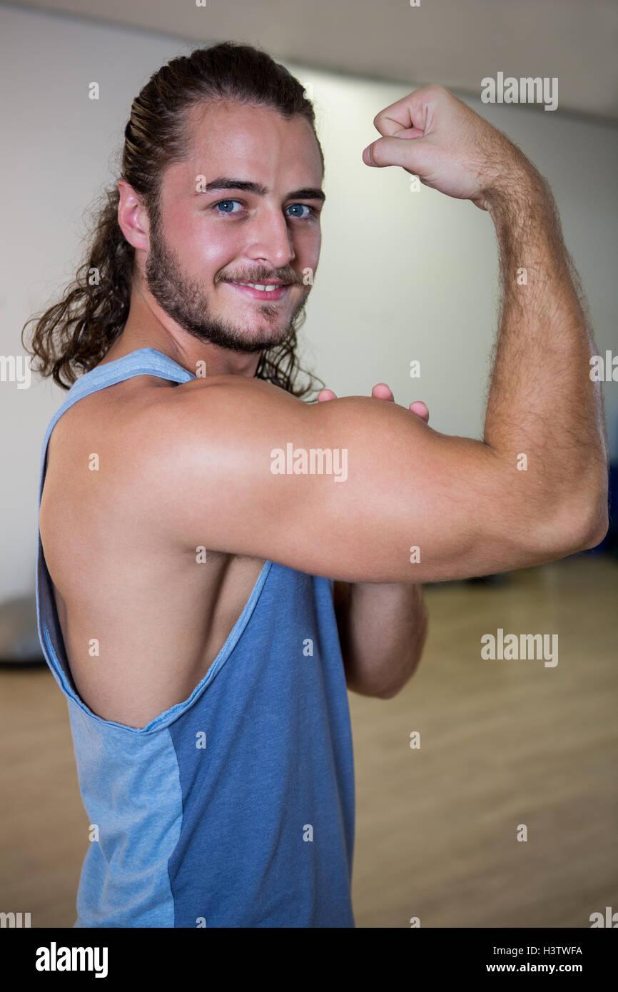 Retrato del hombre sonriente flexionando sus bíceps Foto de stock