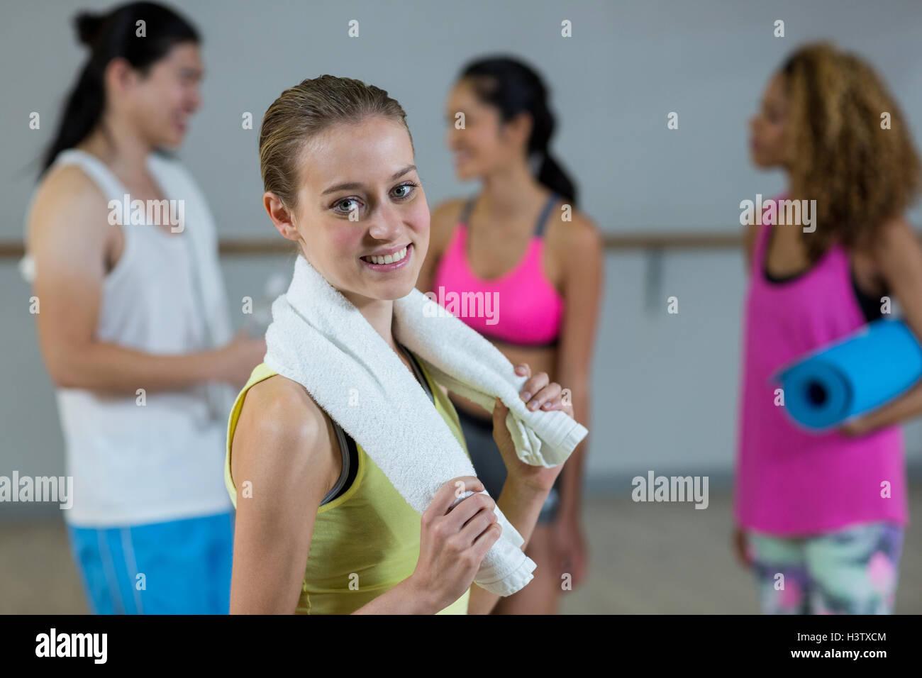 Retrato de mujer trainer sosteniendo la toalla con clase de gimnasia en segundo plano. Imagen De Stock