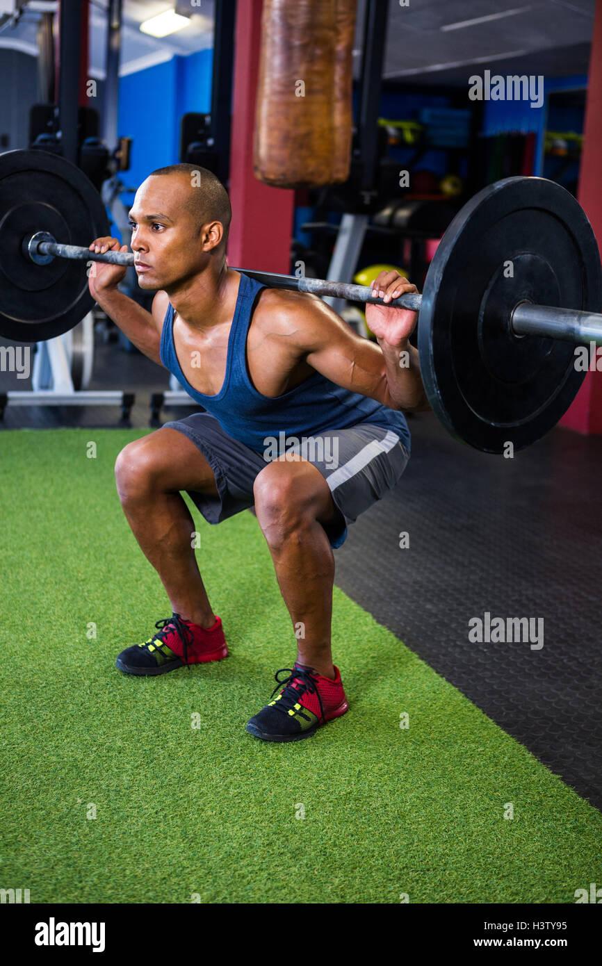 Joven de levantamiento de pesas en el gimnasio Imagen De Stock