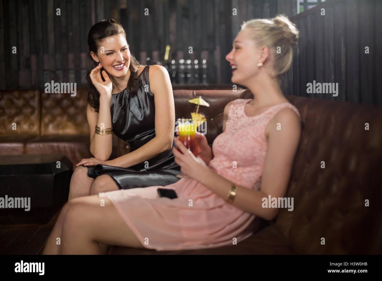 Amigas interactuando entre sí teniendo cóctel Imagen De Stock