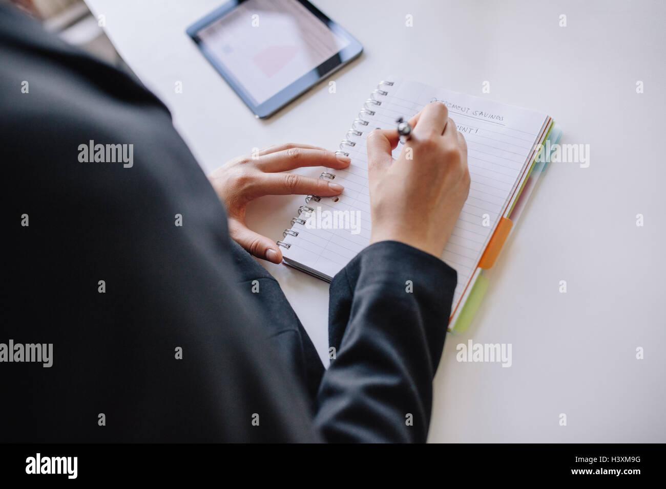 Primer plano de la joven empresaria manos escrito en el bloc de notas en la oficina. Hembra tomando notas en el Imagen De Stock