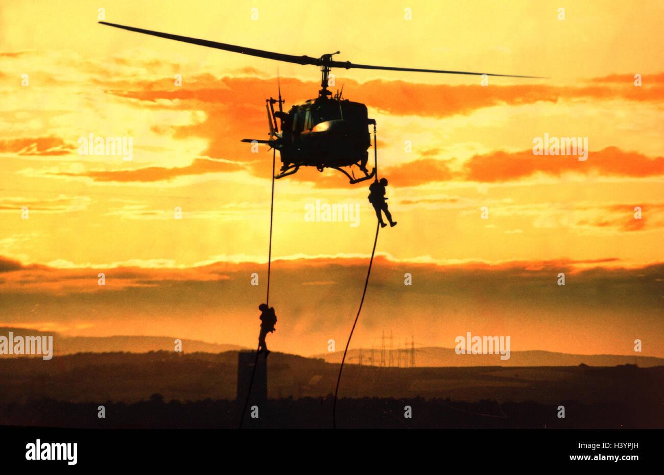 Un helicóptero militar. Helicópteros de combate, silueta, soldado, cuerda, los militares, la fuerza de Imagen De Stock