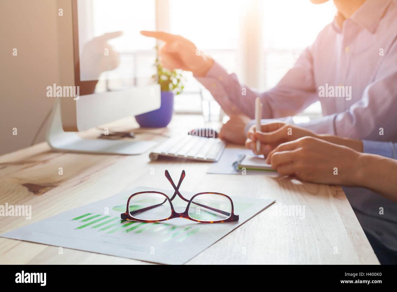 Puesta del sol en la atmósfera de trabajo co-oficina, reunión de negocios con dos personas, más cerca de las gafas Foto de stock