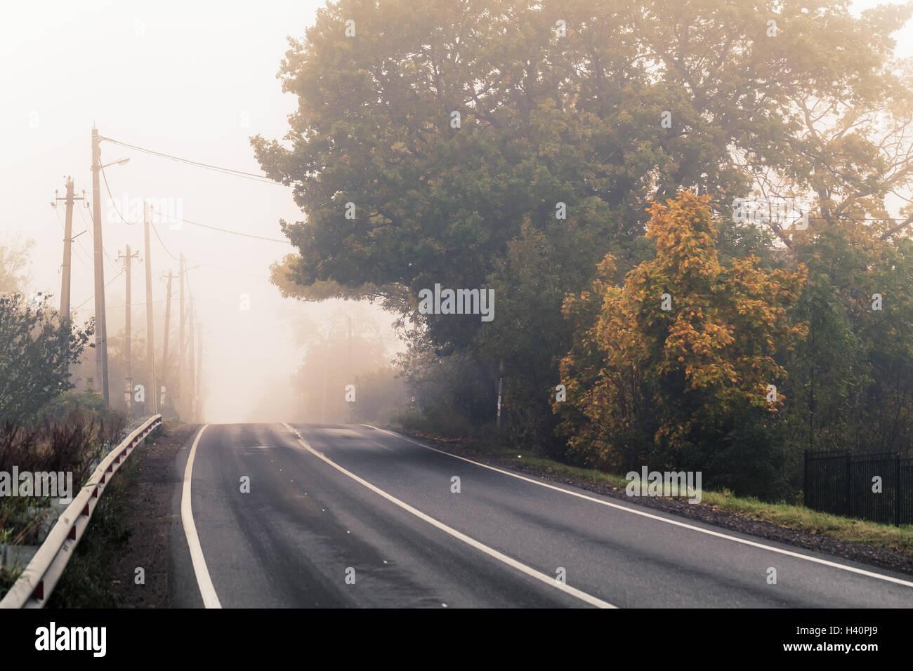 Vacía la autopista rural en otoño de niebla por la mañana y estilizados foto con el efecto de corrección tonal cálida, antiguo filtro estilo instagram Foto de stock