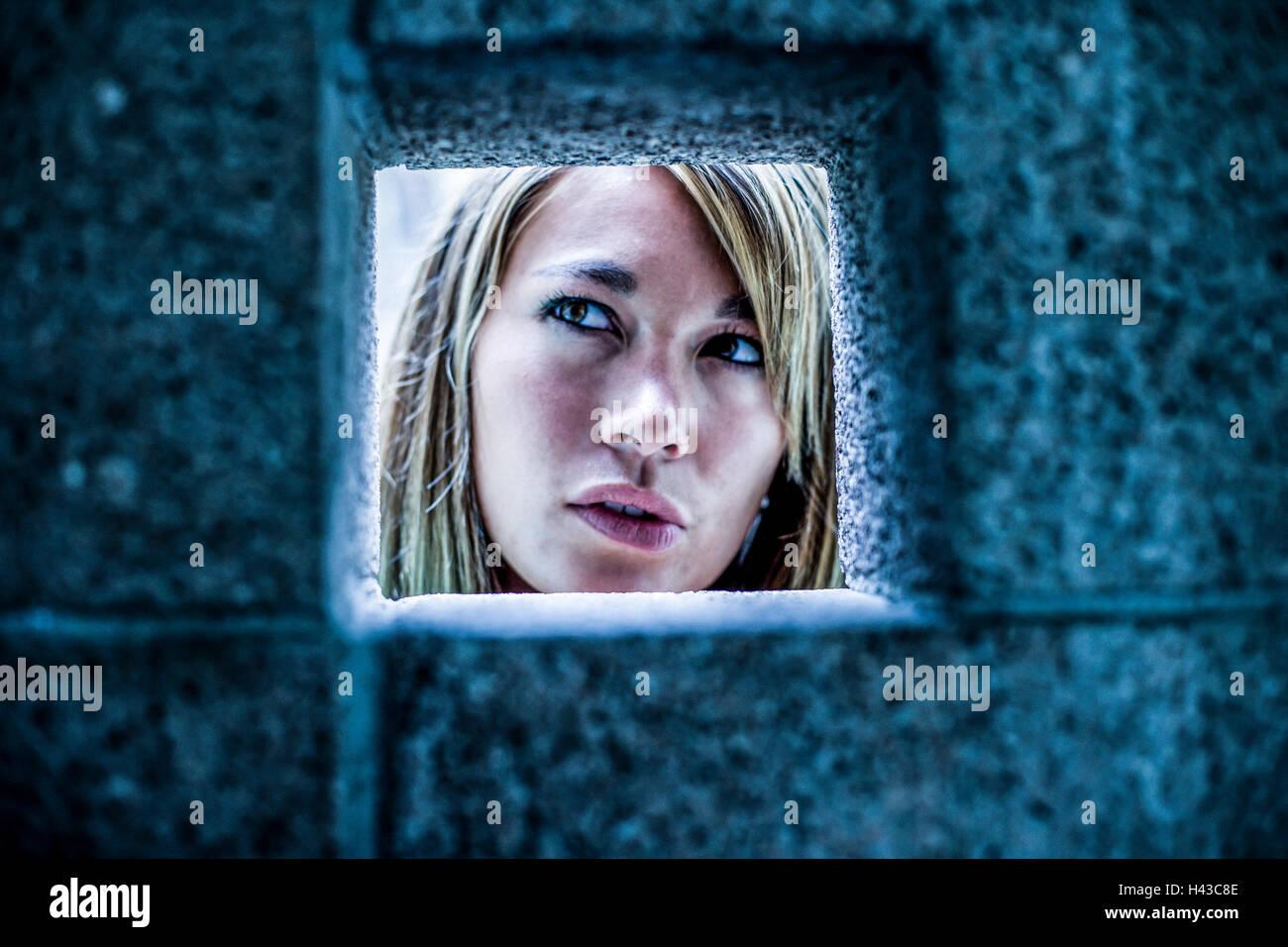 Curiosa raza mixta mujer mirando a través de la pared de piedra Foto de stock