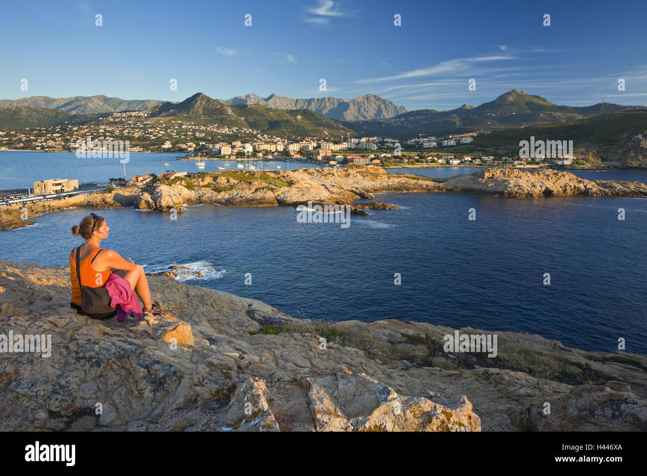 Francia, Córcega, L'Ile Rousse, rock coast, mujer, relajación, vista posterior, Imagen De Stock