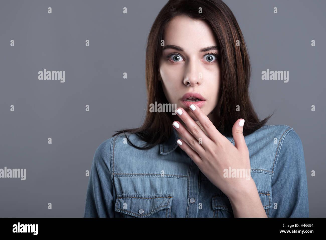 Asustada joven levantando la mano a la boca Imagen De Stock