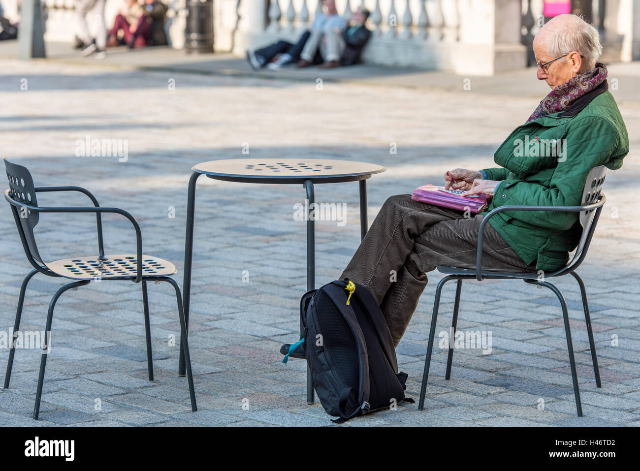 a422ad7aa60b6 Un anciano hombre sentado por sí mismo haciendo un crucigrama en el patio  del Somerset House