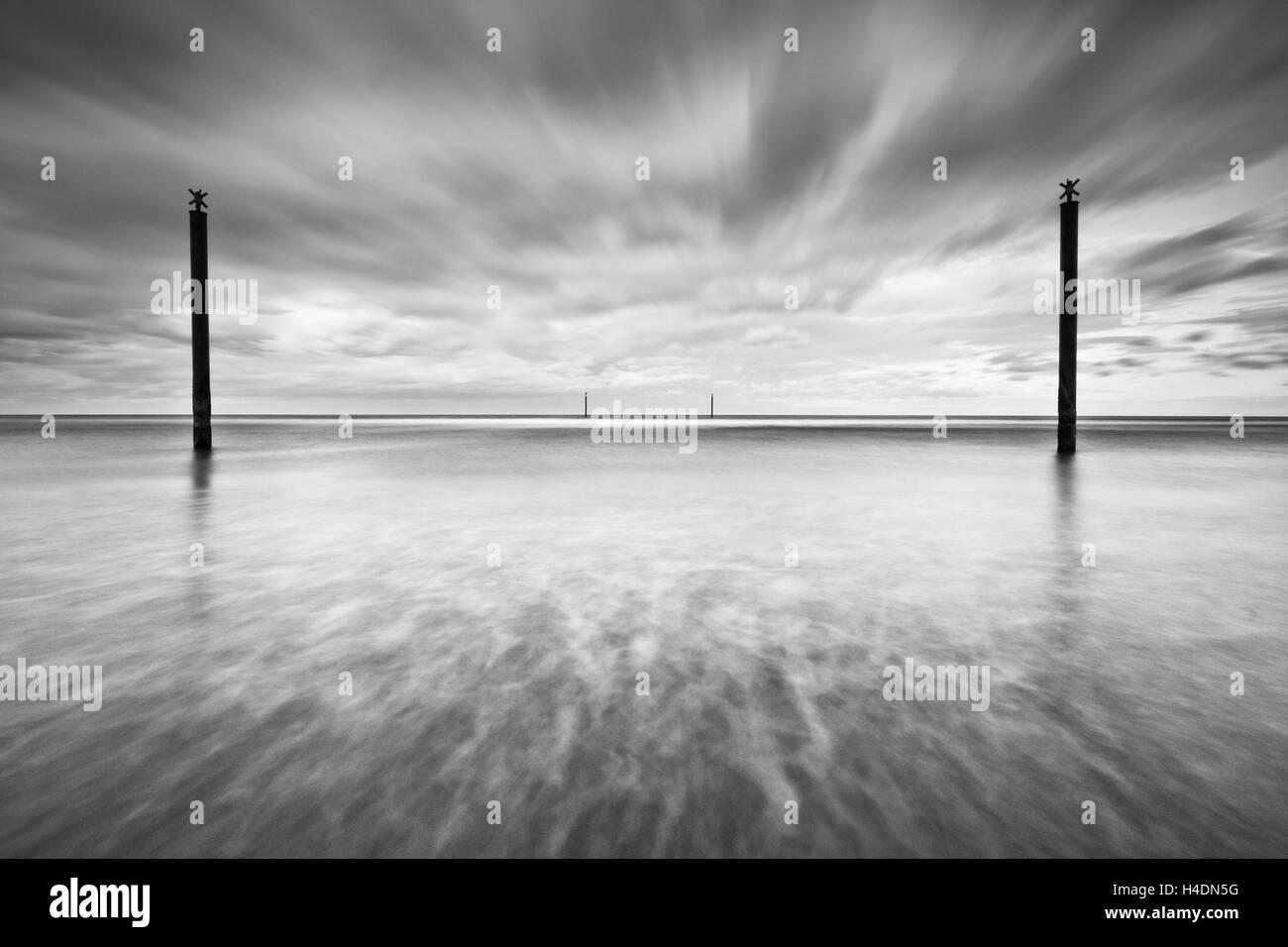Postes guía de navegación en el Mar del Norte frente a la costa de Northumberland en un día nublado, la larga exposición efecto creativo Foto de stock