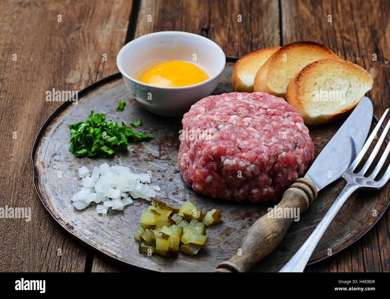Tartar de carne de vacuno fresca con huevo, encurtido de pepino y cebolla. Enfoque selectivo Imagen De Stock
