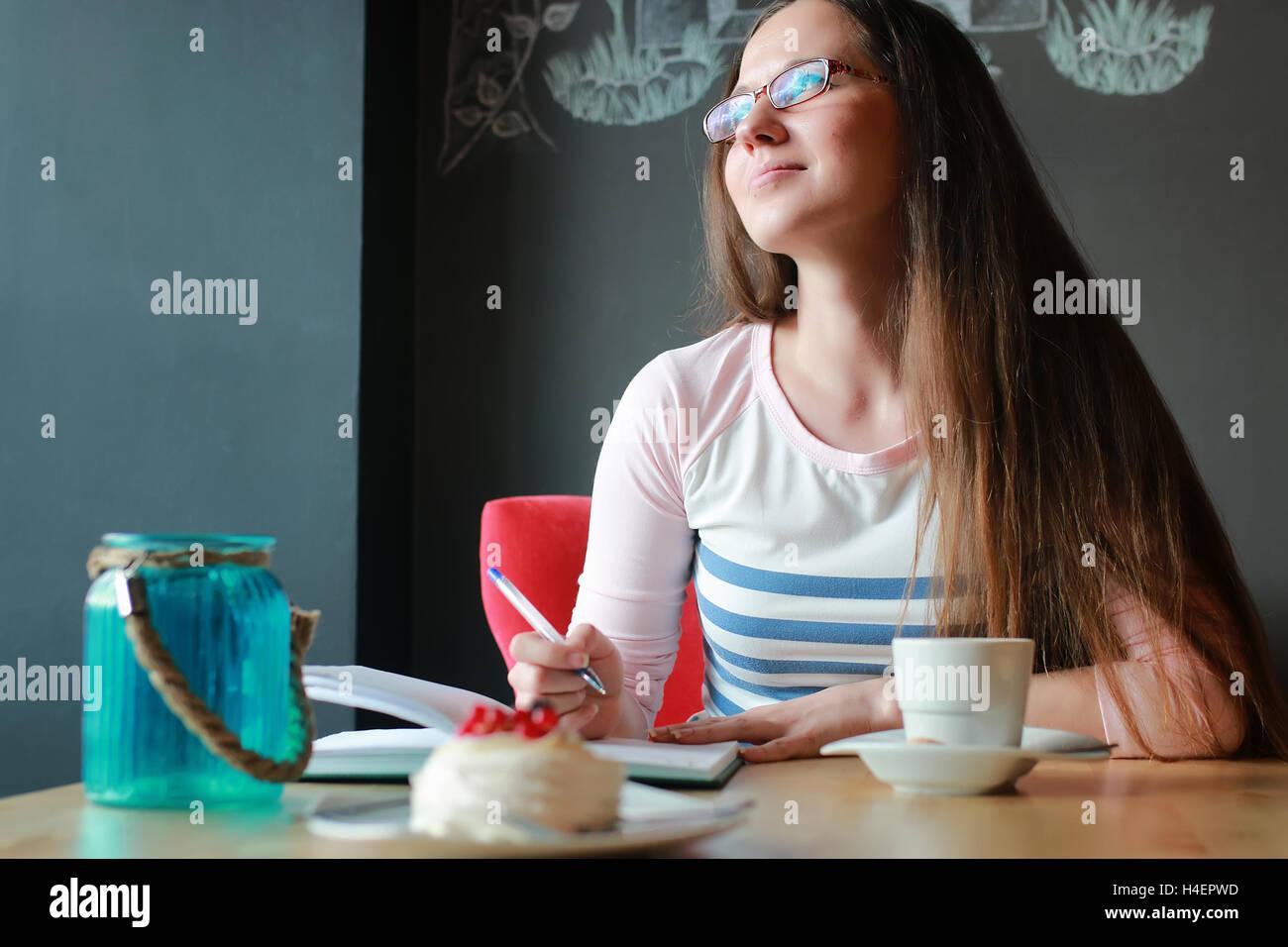 Chica en un café para una taza de café con el portátil Imagen De Stock