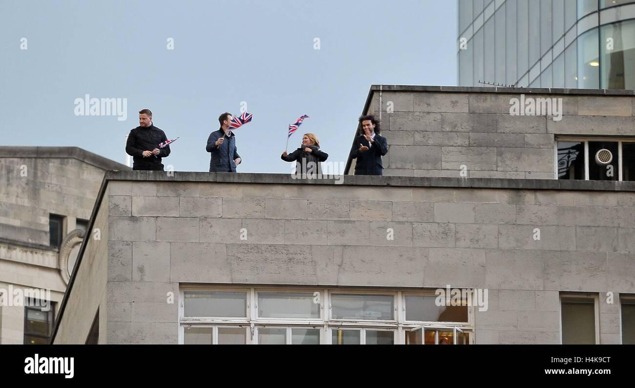 Manchester, Reino Unido. 17 Oct, 2016. Los espectadores ola sus banderas sindicales desde los tejados de Manchester. Foto de stock