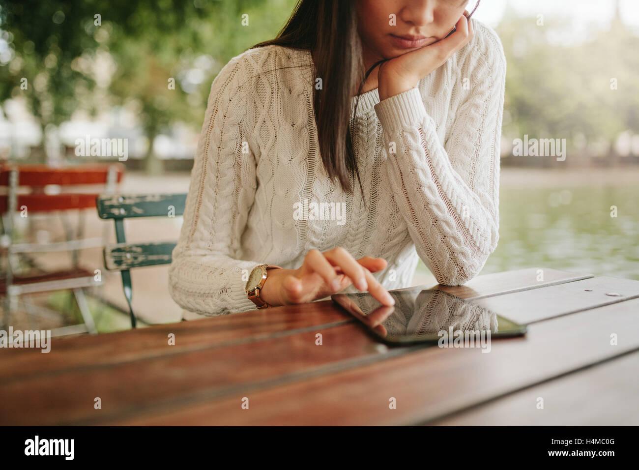 Mujer joven con tableta digital en la cafetería al aire libre. Navegando páginas web hembra de panel táctil Imagen De Stock
