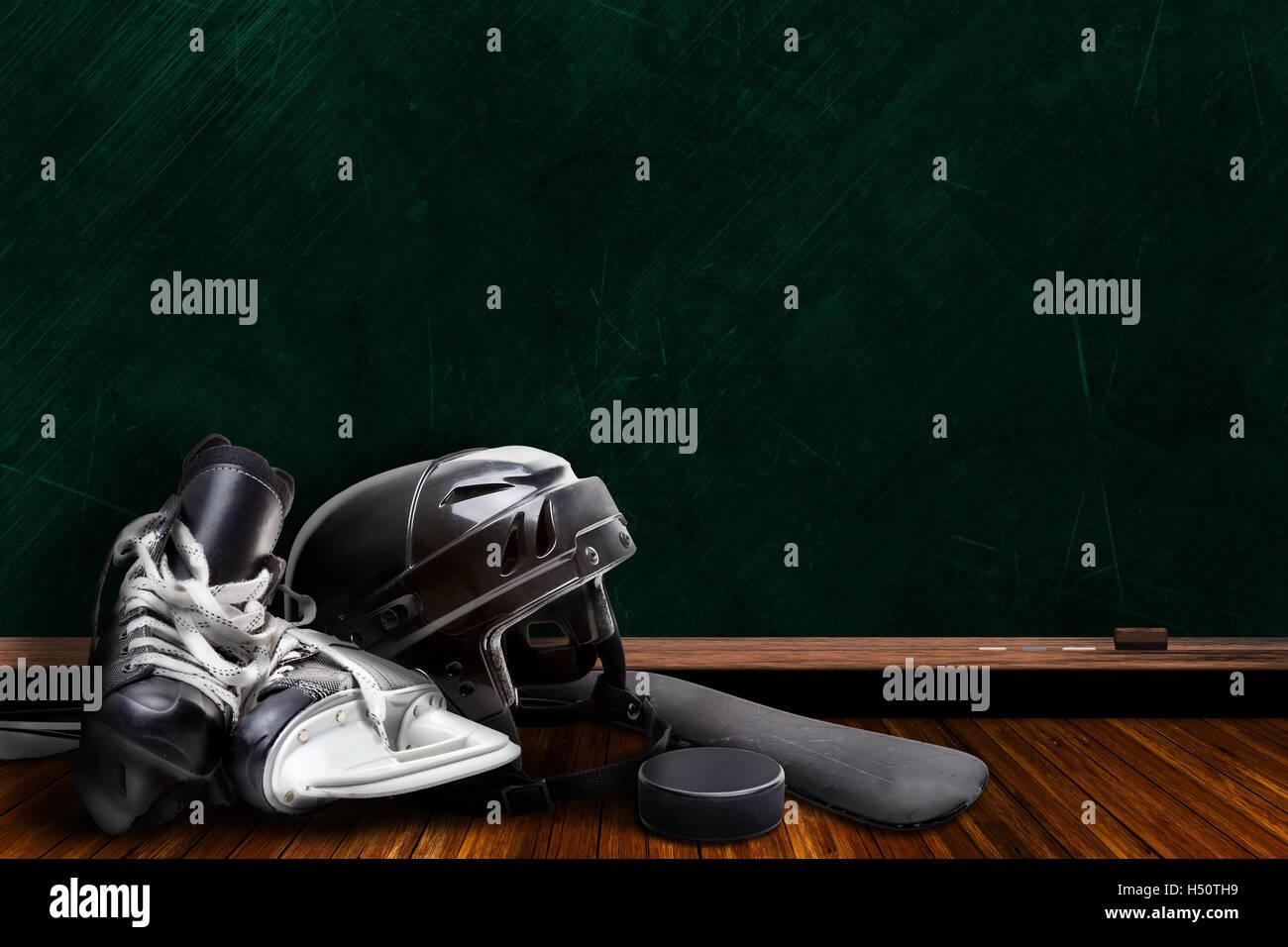 El equipo de hockey sobre hielo compuesto de patines, casco, stick y el puck con pizarra de fondo copia el espacio. Imagen De Stock