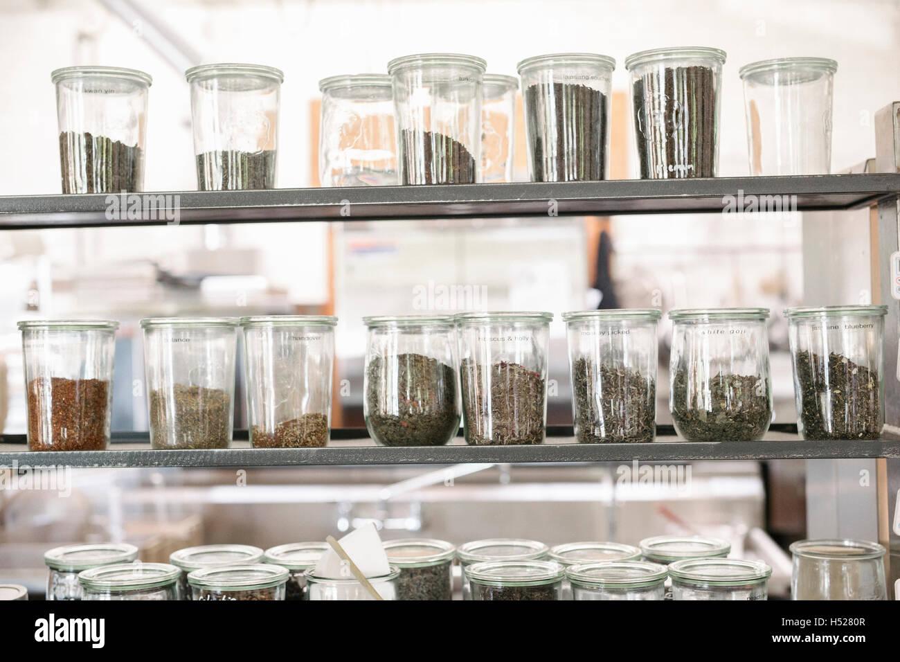 Una selección de alimentos secos y condimentos en tarros de vidrio en  estantes en una cafetería 1245cfc523b4