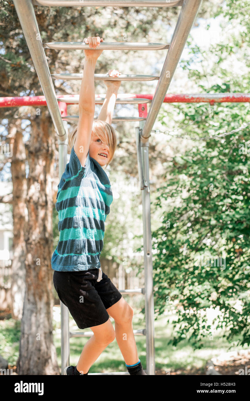 Muchacho rubio en un marco de escalada en un jardín Foto & Imagen De ...