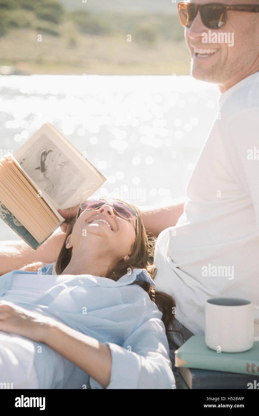 Hombre y mujer recostado sobre un embarcadero, leyendo un libro. Imagen De Stock
