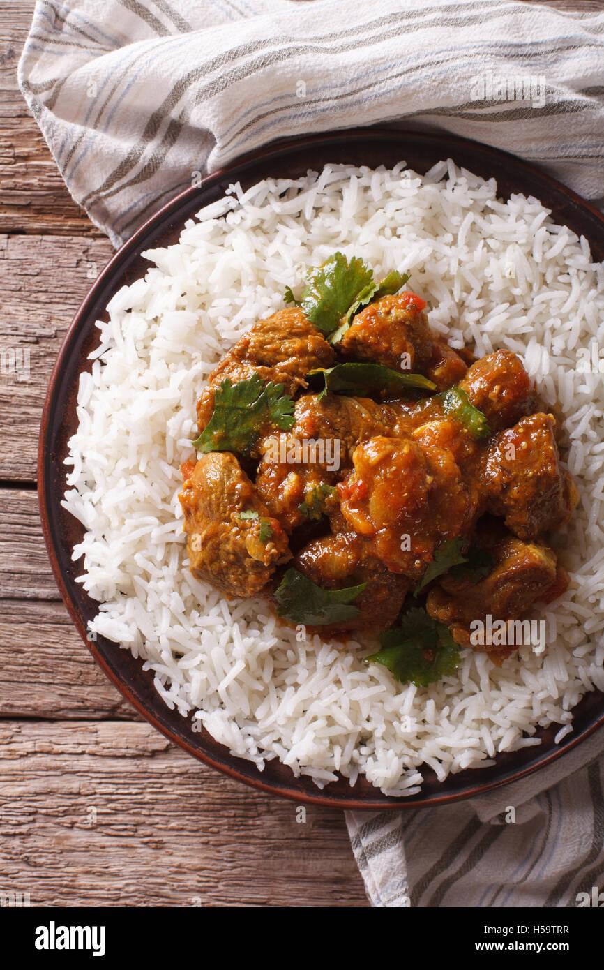 Comida india: Madras ternera con arroz basmati en la tabla cerca. vista vertical desde arriba Imagen De Stock