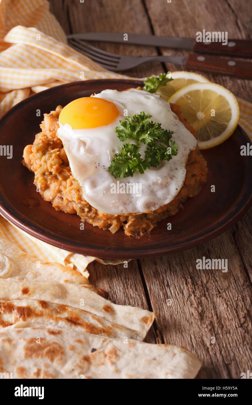 Desayuno: ful medames árabe con un huevo frito en una placa cerca. Vertical Imagen De Stock