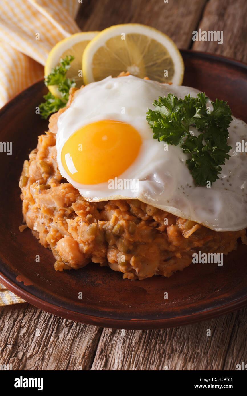 Cocina árabe: ful medames con huevo frito en una placa vertical de cerca. Imagen De Stock