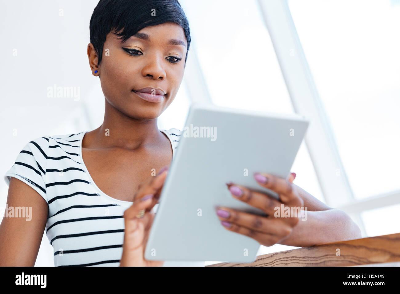 Atractiva empresaria afro americana con tablet PC en la oficina Imagen De Stock