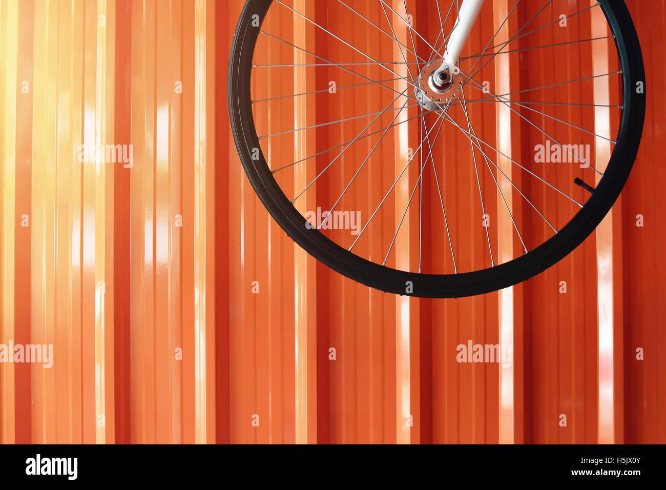 Rueda de la bicicleta colgando en la pared del garaje naranja Imagen De Stock