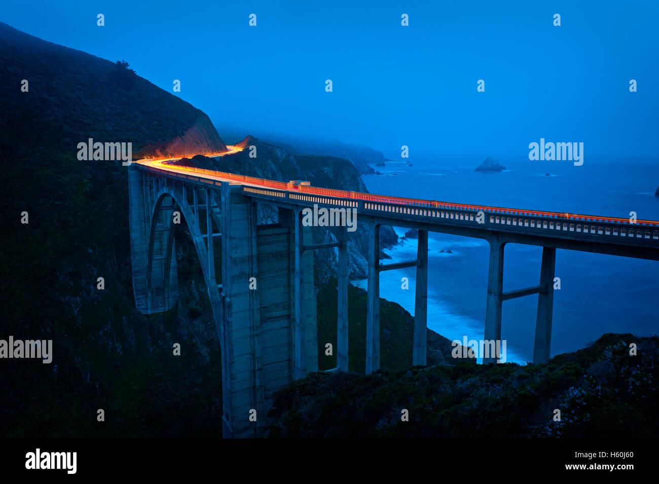 Alquiler lighttrails al atardecer en Bixby Creek Bridge Imagen De Stock