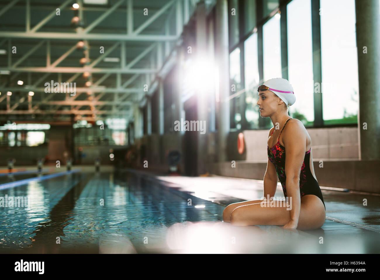 Vista lateral de disparo colocar joven nadador relajarse al borde de una piscina. Imagen De Stock