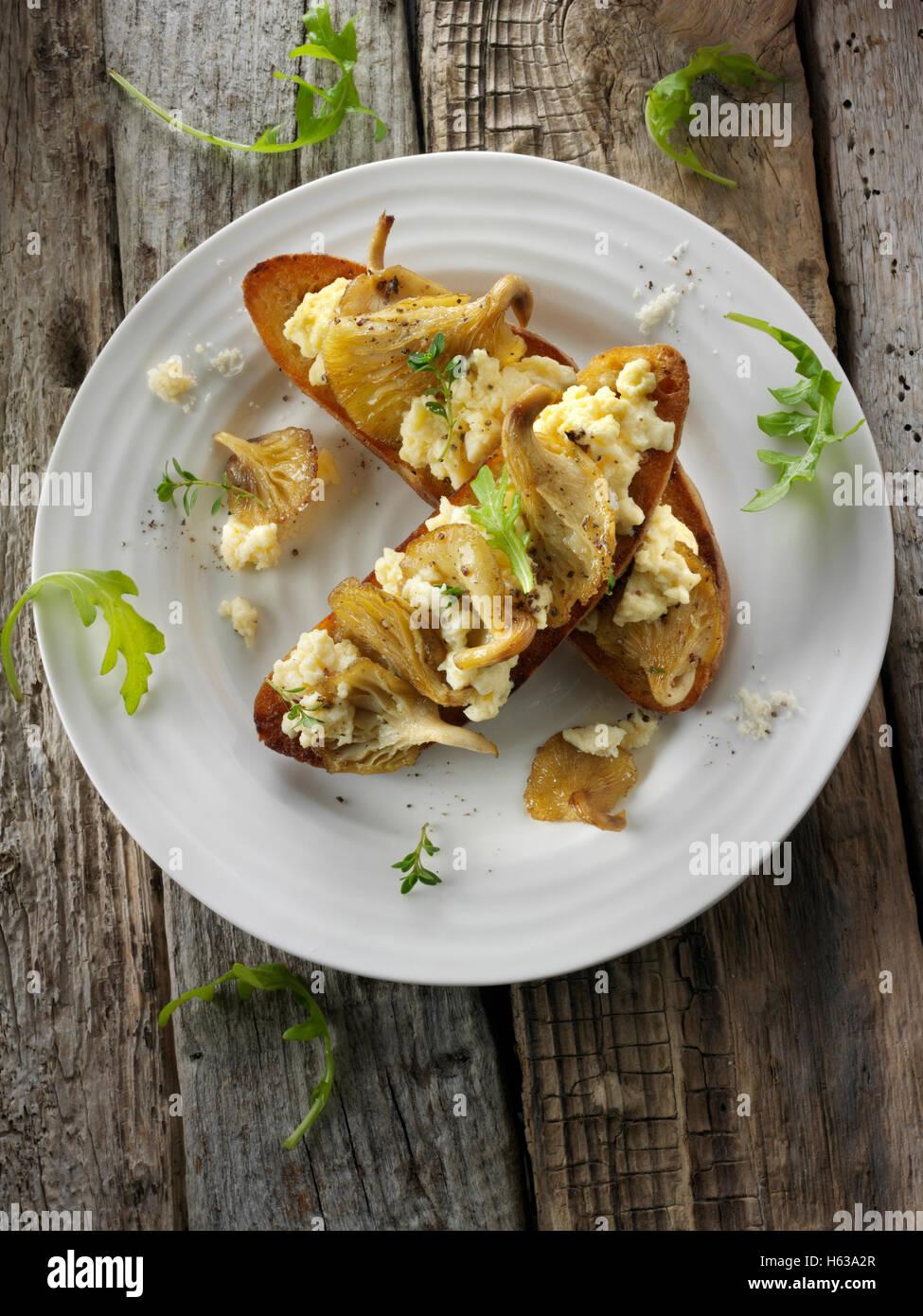Amarillo setas salteadas en mantequilla y servido con huevo scambled en masa agria tostadas con Wild Rocket Imagen De Stock
